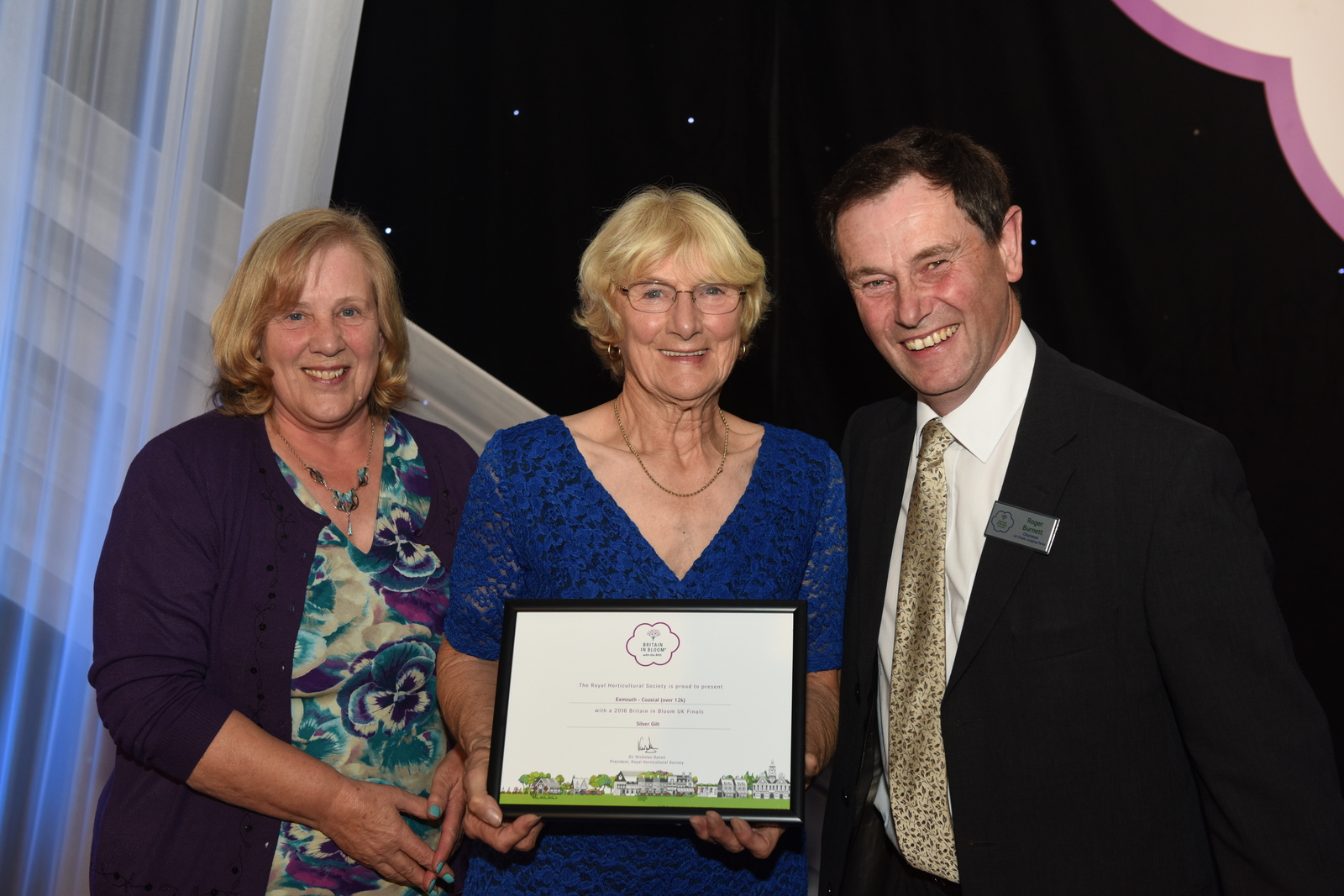 Roger Burnett presents the silver gilt award to Pat Graham and Ann Wheeler